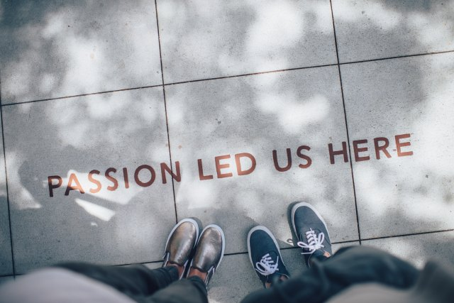 "2 pairs of feet on a sidewalk near the words ""passion led us here"""