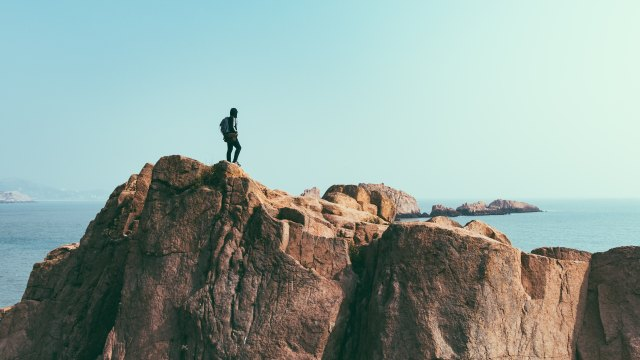 Hiker on a cliff overlooking the ocean