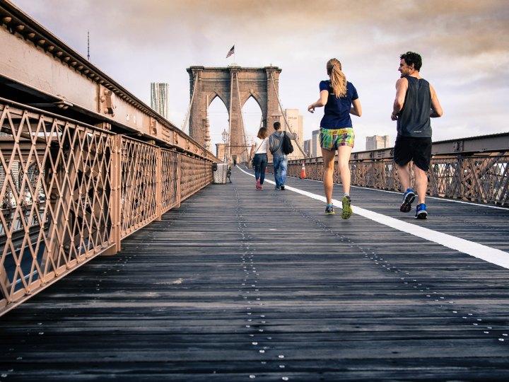 two people jogging across a bridge