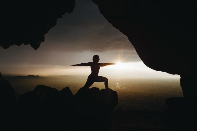 A person in a yoga pose on a rock overlooking the ocean