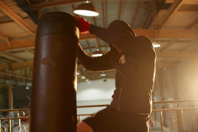 A guy kneeing a boxing bag