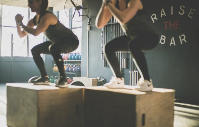 two girls completing a box jump at a gym