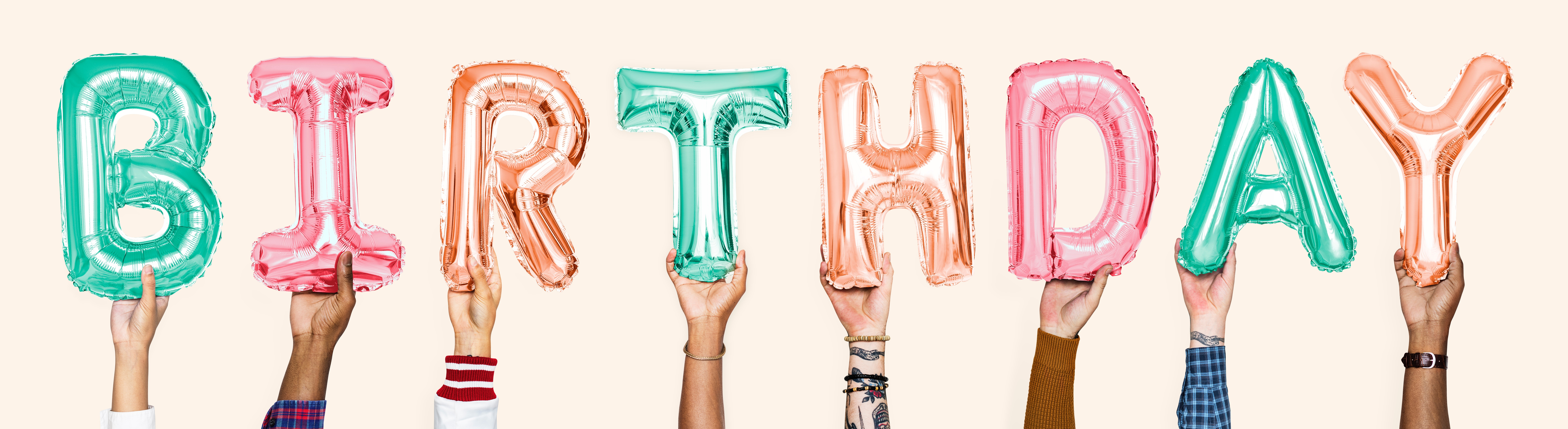 hands holding up balloons that spell out 'birthday'