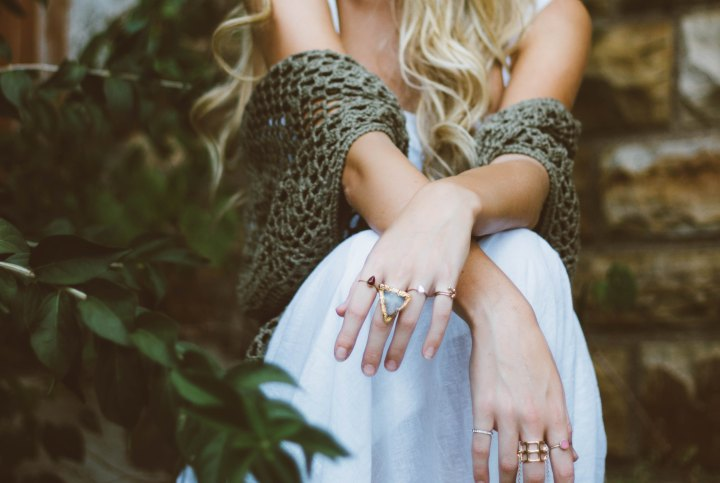 A girls hands with a bunch of rings on them