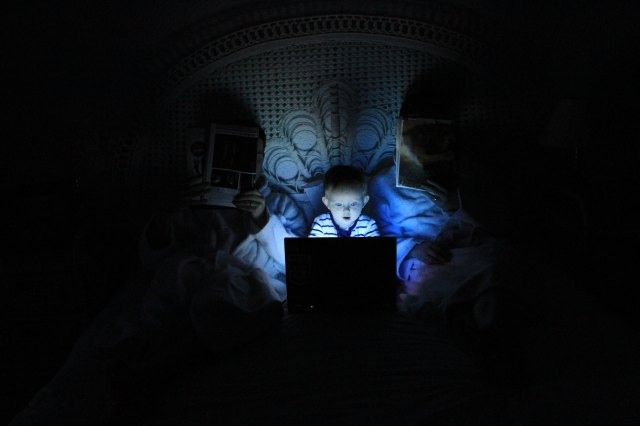 A boy on the computer at night