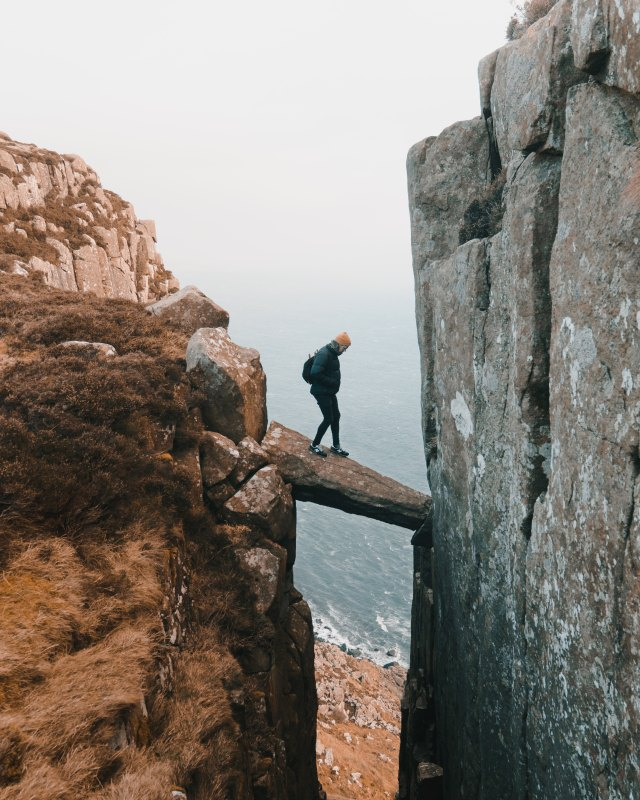 A man standing on a piece of wood connecting two cliffs.