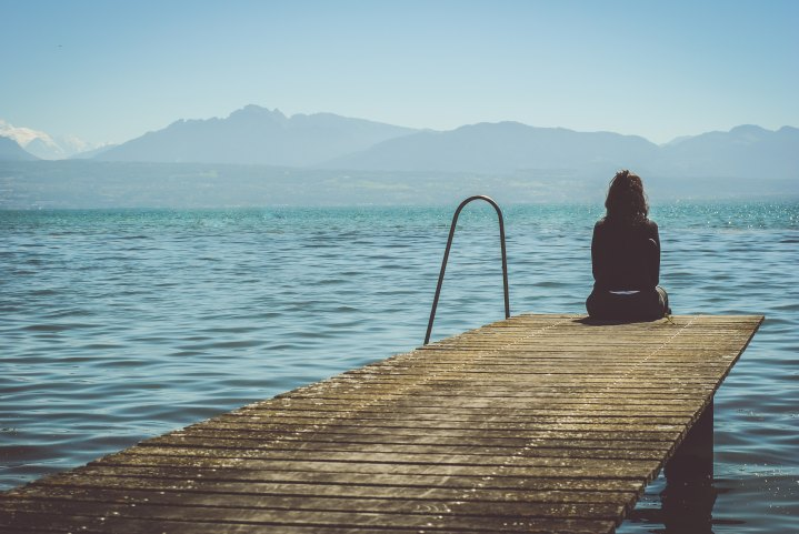 A girl sitting on a dock looking out over the water